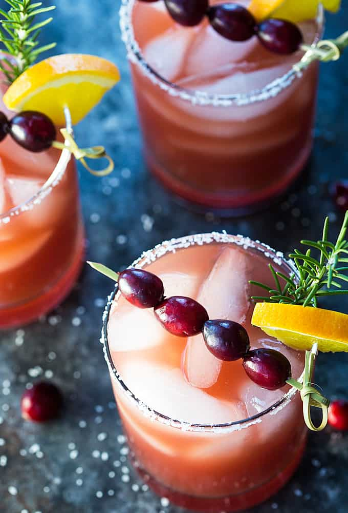 Three margaritas garnished with a skewer of cranberries, orange and rosemary.