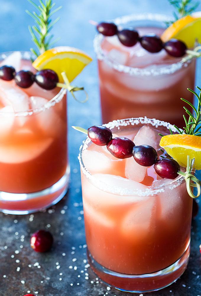 Front view of three cranberry orange margaritas in salt-rimmed glasses.