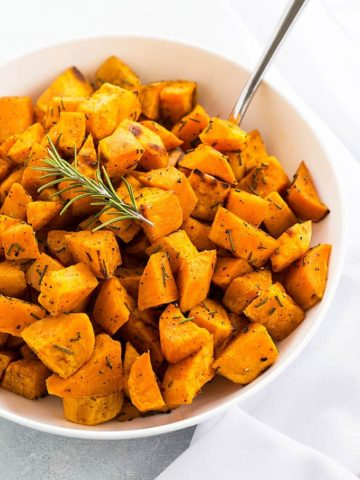 Roasted bite size pieces of sweet potatoes with rosemary in a white bowl.