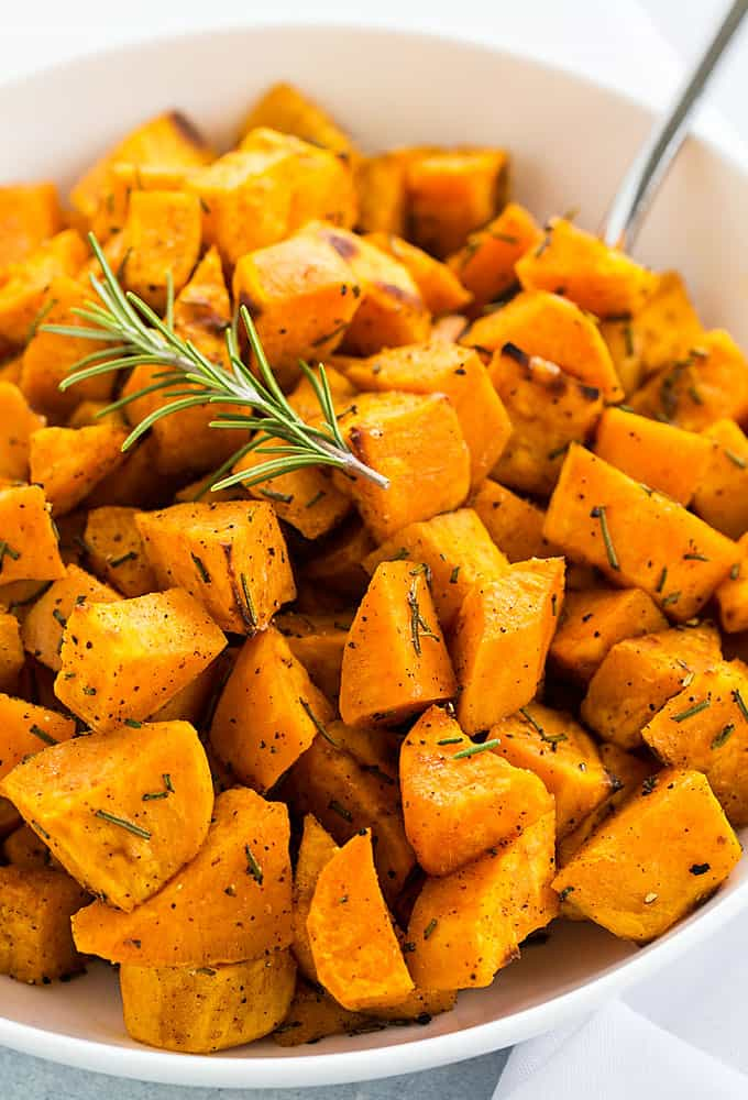A closeup of roasted rosemary sweet potatoes in a white bowl.