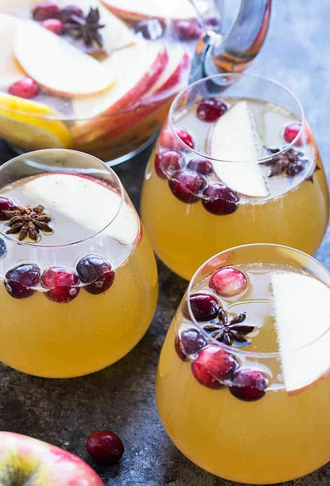 Three glasses of sangria with cranberries and star anise.