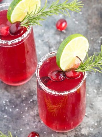 Two garnished cranberry mimosa margaritas in salt-rimmed glasses.
