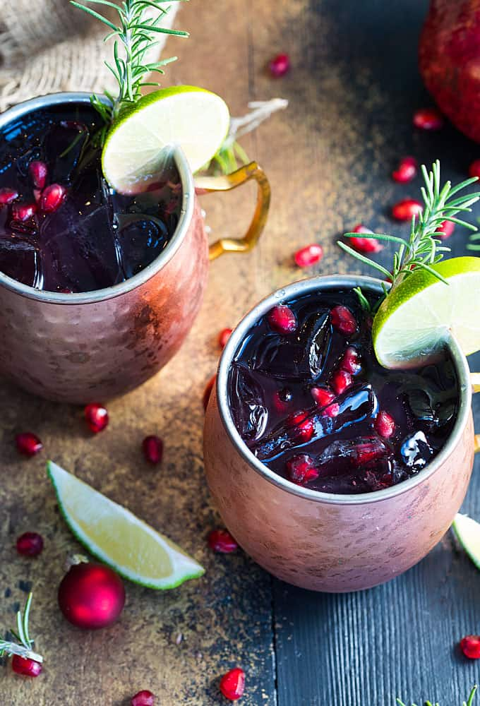 Overhead view of two copper mugs of pomegranate moscow mules on a dark surface.