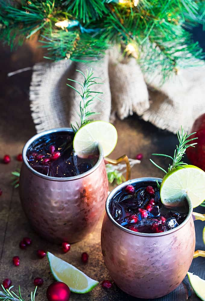 Two pomegranate moscow mules by a small decorative holiday tree.