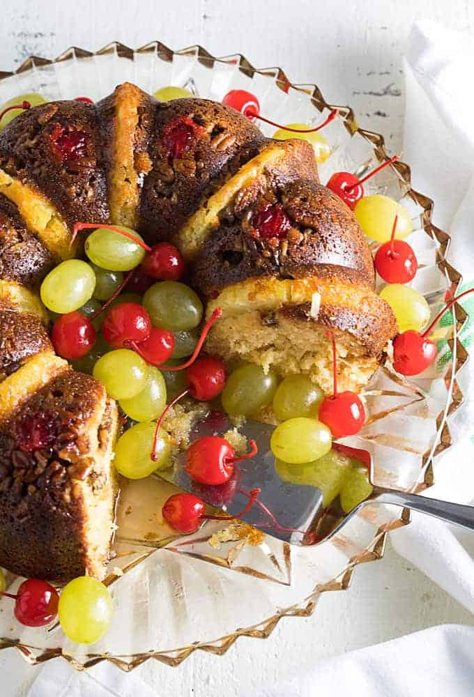 Overhead view of a rum bundt cake with cherries and grapes on a platter.