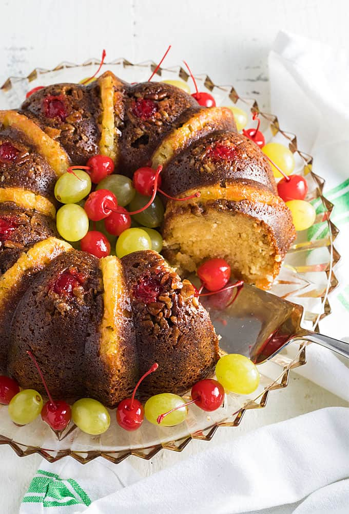 Overhead view of a rum cake with pineapple, cherries and grapes on a glass platter.
