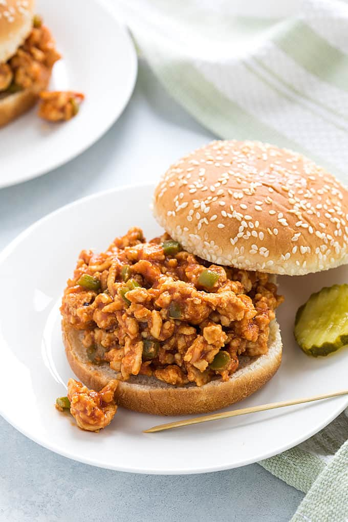 An open-faced sloppy joe sandwich on a white plate.