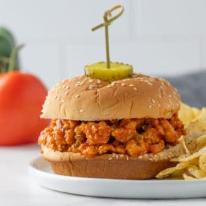 Front view of a turkey sloppy joe sandwich on a plate with potato chips.