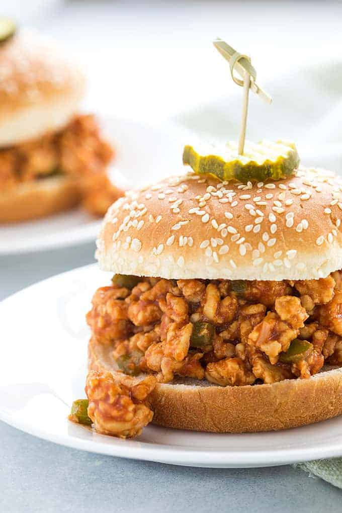 Front closeup view of a sloppy joe sandwich on a white plate.