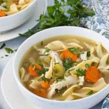 A white bowl of chicken noodle soup on a plate beside a patterned napkin.