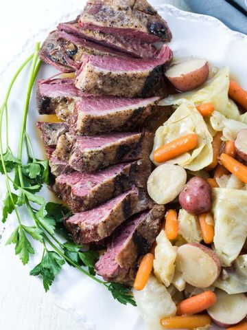 Overhead view of sliced corned beef, cabbage, potatoes and carrots on a white platter.