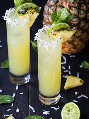 Two mojitos garnished with pineapple, lime and mint in glasses rimmed with flaked coconut.