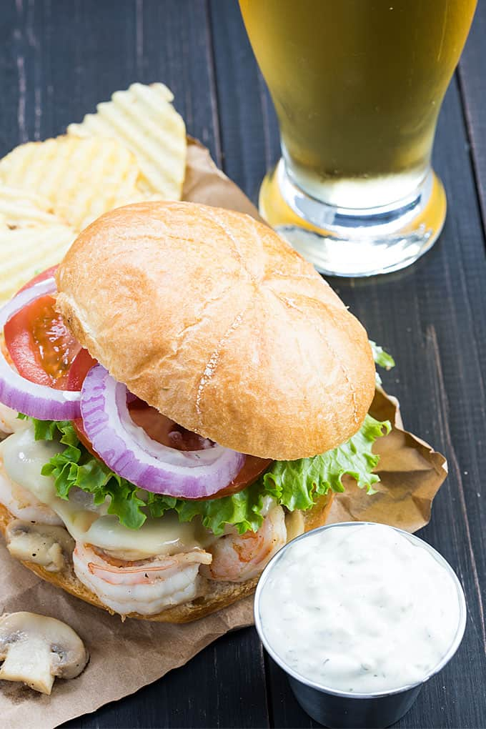 Tartar sauce in a condiment cup beside a shrimp burger and a glass of beer.