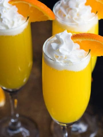 Three creamsicle mimosas with whipped topping and an orange slice in champagne flutes.