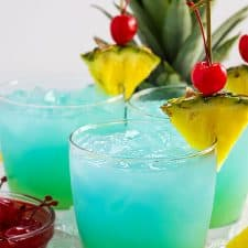 Front view of three blue and green cocktails garnished with pineapple and cherries.