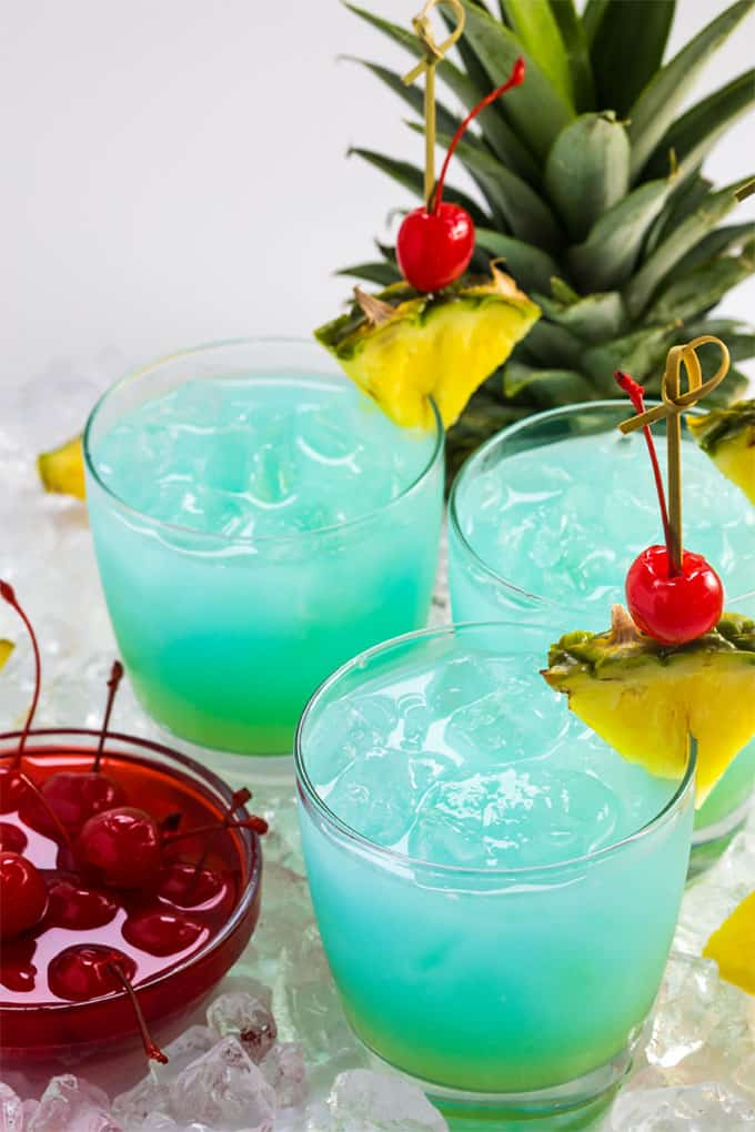 Three blue and green cocktails by a bowl of maraschino cherries.