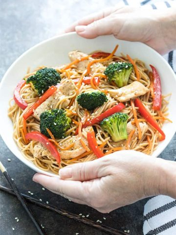 Two hands holding a white bowl of chicken and broccoli lo mein over a dark surface.