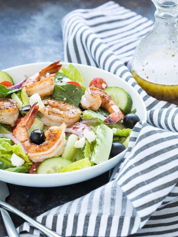A white bowl of salad with shrimp beside a bottle of Greek dressing and a napkin.