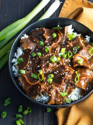 Overhead view of Mongolian beef over rice in a black bowl.
