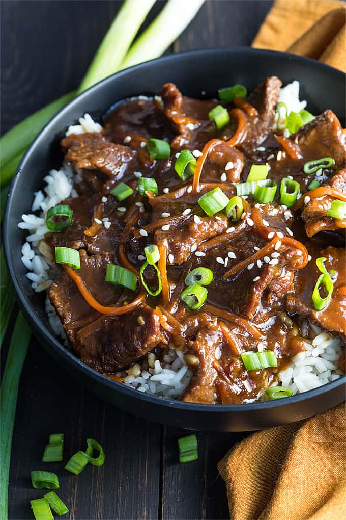 A closeup of Mongolian beef over rice and topped with green onions in a black bowl.