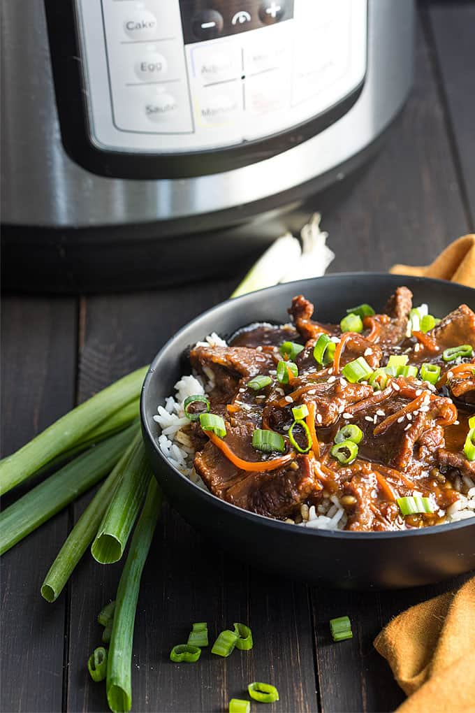 A bowl of Mongolian beef over rice.  An instant pot is in the background.
