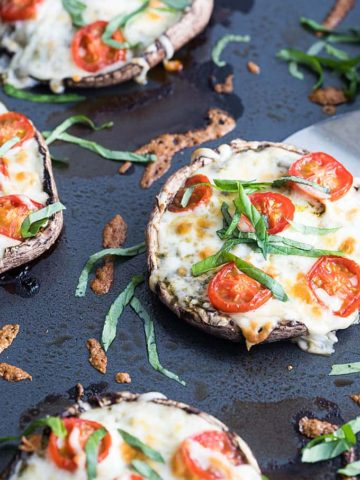 A closeup of baked portobello mushroom caps topped with cheese, tomatoes and basil.