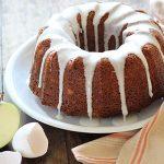 A glazed bundt cake on a plate beside a striped napkin.
