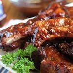 Barbecue ribs on a white plate with a sprig of parsley.