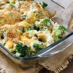 Broccoli au gratin in a glass baking dish with a wooden spoon.