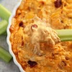 A celery stick dipped into a dish of chicken dip.  Overlay text at top of image.