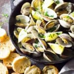 Overhead view of steamed clams in a cast iron skillet by toasted French bread.