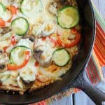 Overhead closeup view of a vegetable pizza in a cast iron skillet.