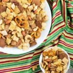 Overhead view of party snack mix in two white bowls on a striped napkin.