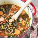 Soup with sausage, black-eyed peas and collards in a red dutch oven with a wooden spoon.