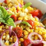 Closeup of corn salad with tomatoes, red onion and basil in a white bowl.