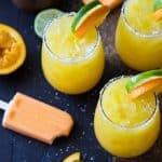 Overhead view of three margaritas garnished with orange and lime slices.