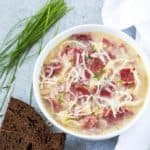 Overhead view of a white bowl of soup with corned beef, sauerkraut shredded Swiss cheese.