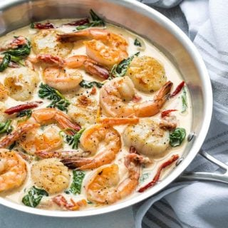 Creamy Tuscan Shrimp and Scallops - Shrimp and scallops in a garlicky Parmesan cream sauce with sun dried tomatoes and spinach - Ready in just 20 minutes!