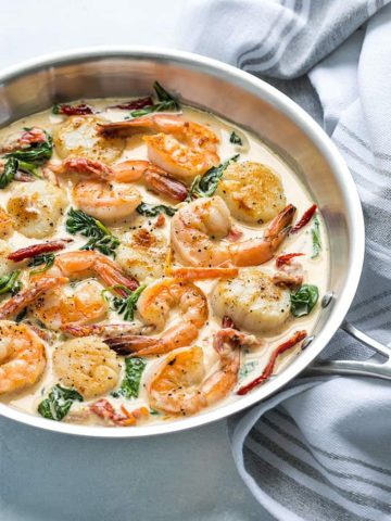 Shrimp and scallops in a cream sauce with spinach and sun-dried tomatoes in a skillet.