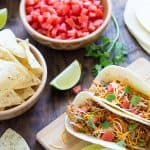 Two soft chicken tacos, a bowl of diced tomatoes and a bowl of tortilla chips.