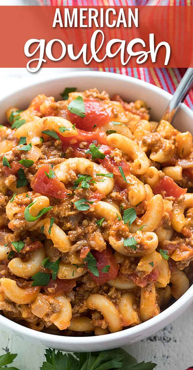 Overhead closeup view of goulash with ground beef and tomatoes in a white bowl.