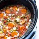 Closeup view of vegetable soup in an oval slow cooker.