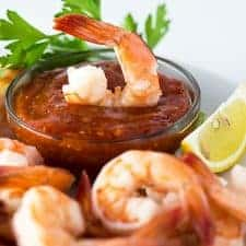A shrimp dipped in a glass bowl of cocktail sauce.