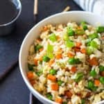 Overhead view of fried rice with vegetables in a white bowl by a pair of chopsticks.