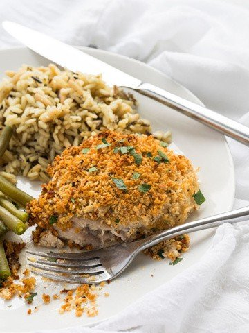 A cut piece of herb breaded chicken on a plate with a fork and knife.
