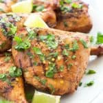 A closeup view of a grilled chicken thigh with chopped cilantro and lime wedges.