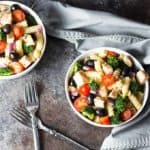Overhead view of pasta salad with vegetables and chicken in two white bowls by two forks.