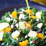 Dressing being poured out a jar on a kale salad with fruit.