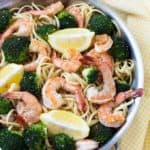 Overhead view of shrimp, broccoli and lemon wedges with pasta in a skillet.