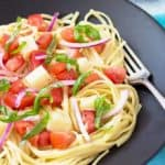 Pasta with tomatoes, mozzarella and red onion on a black plate with a fork.